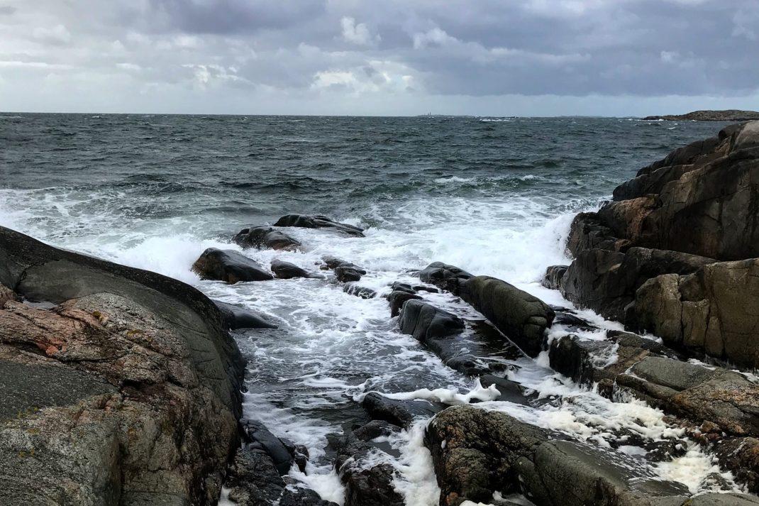En bild på havet som slungar upp skummande vågor mot klipporna.