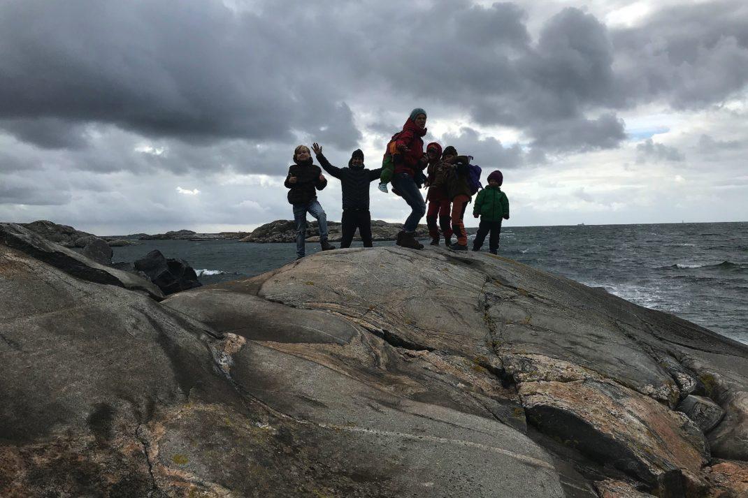 En hop människor står på en klippa med havet i bakgrunden.
