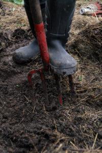 Ett par stövlar gräver i jorden.
