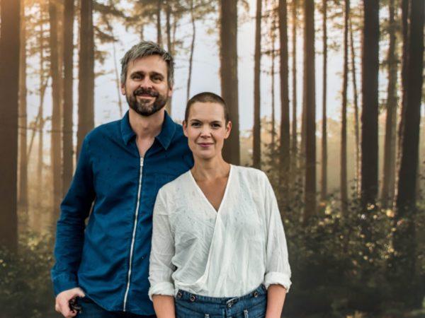 Sara och Johannes står framför en ljus bokskog och tittar in i kameran.