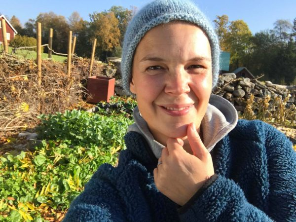 Selfie på Sara Bäckmo som tittar in glatt i kameran framför en höstig köksträdgård.