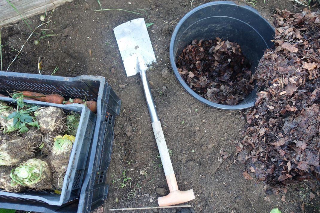 Rotsaker i backar till vänster och till höger en stor kruka nergrävd i jorden. En spade ligger mellan backar och kruka.