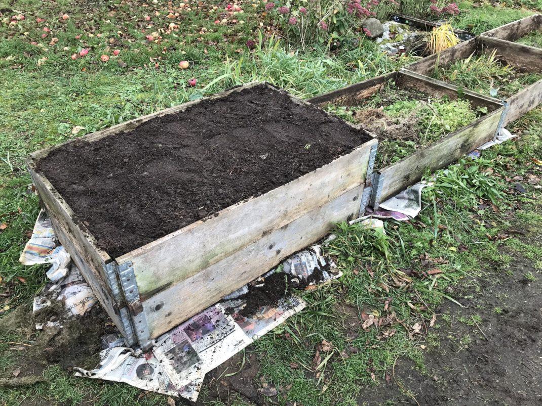 En pallkrage med jord på toppen i trädgården.