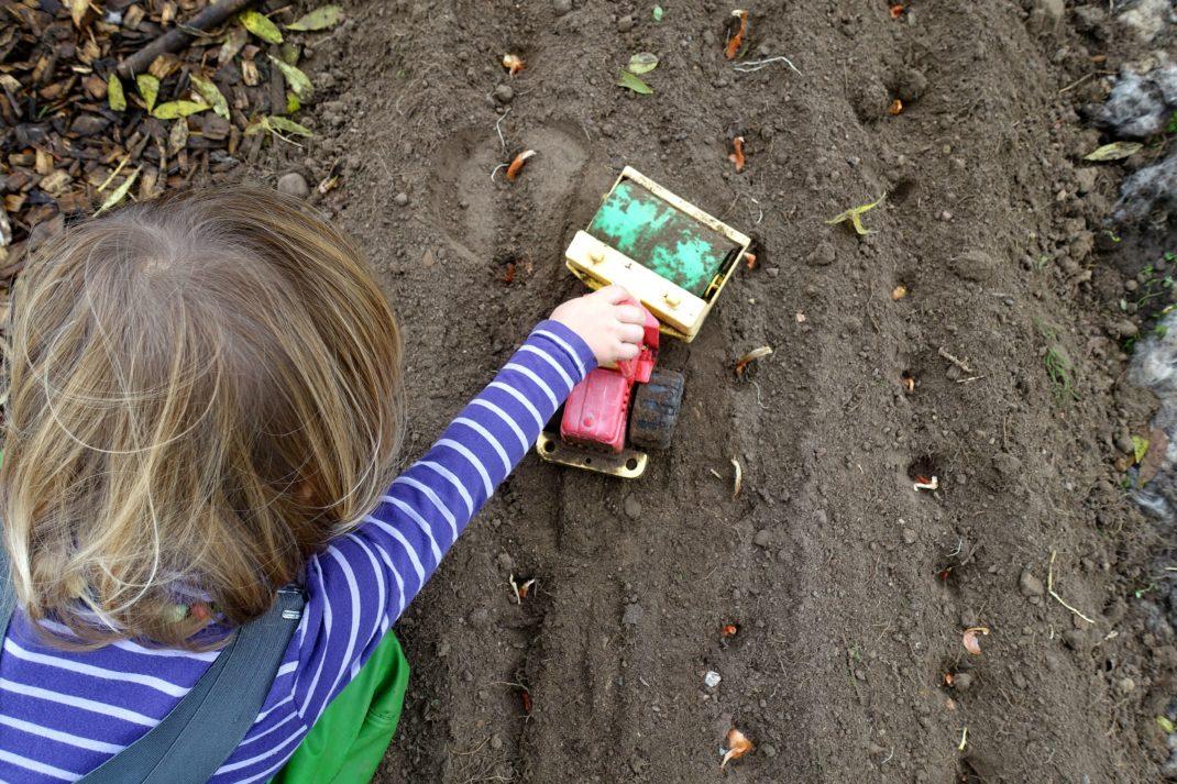 Ett litet barn kör med en leksaksmaskin över jorden i landet.