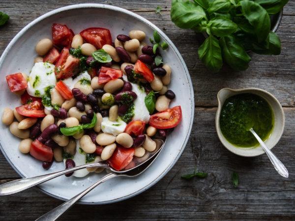 En tallrik med klarröda tomater och bönor i olika färger.