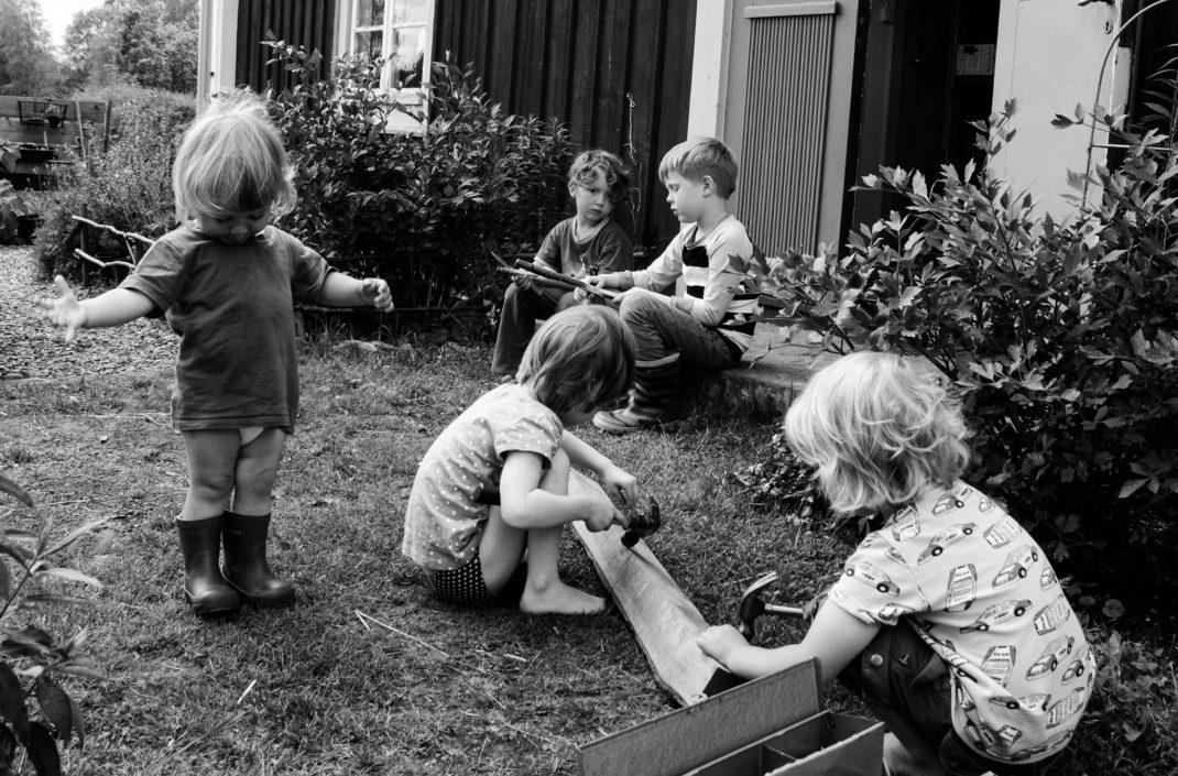 En svartvit bild av fem barn utanför huset i Skillnadens trädgård.