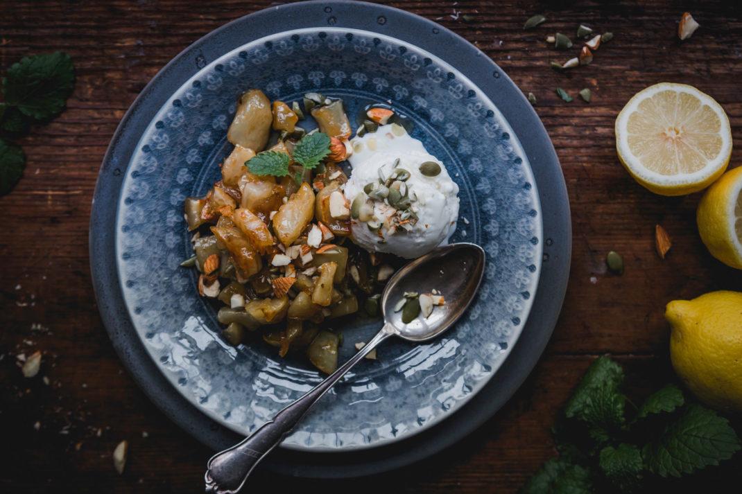 En vacker blågrå tallrik med krispig jordärtskocka och vit vaniljglass.