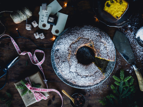 En vackert rund saffranskaka tillsammans med florsocker och jultillbehör.