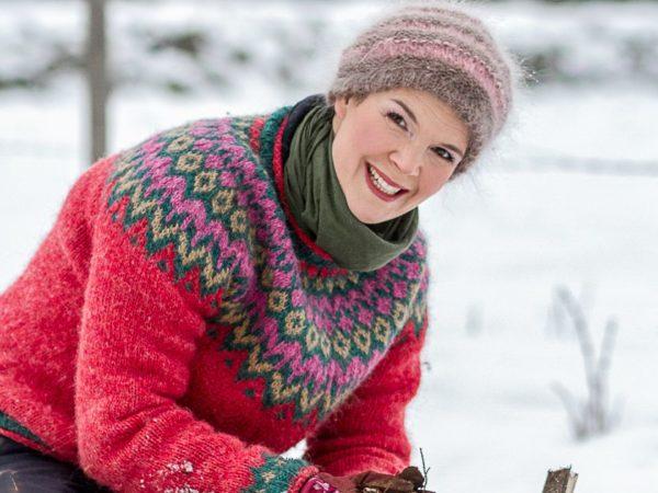 Sara Bäckmo i snön med en vackert mönstrad tröja i rosa grundfärg.
