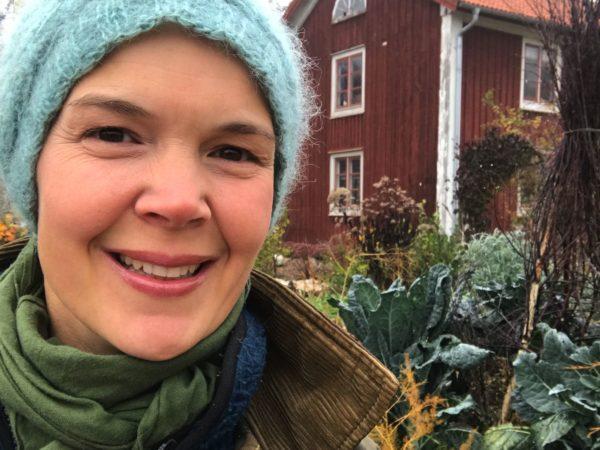 Sara Bäckmo sitter i höstiga kläder i en köksträdgård