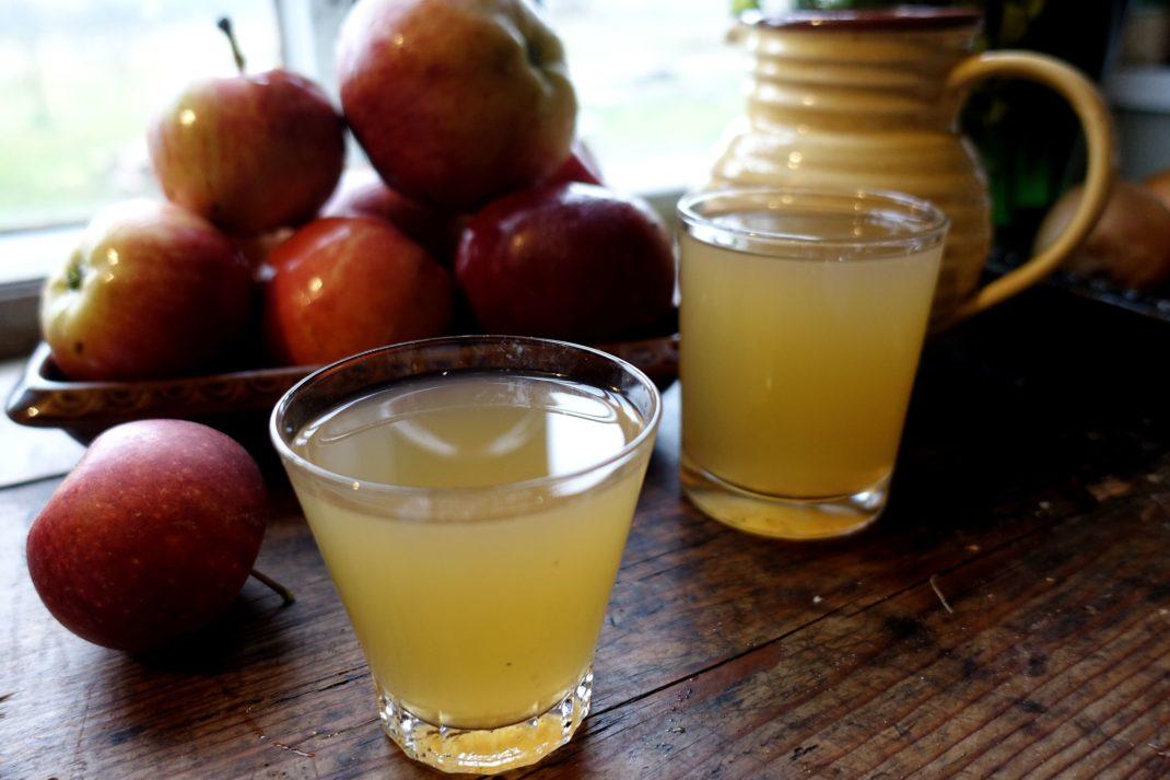 Två glas med äppelmust på ett träbord med en skål äpplen i bakgrunden.