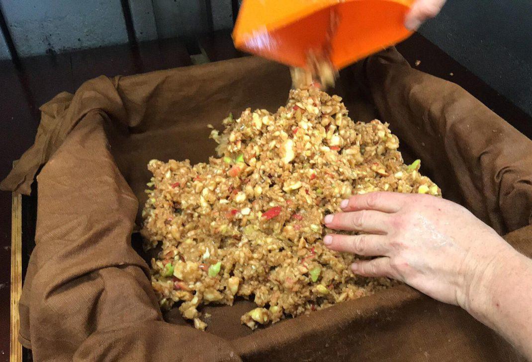 En skopa lägger äppelkross inuti en brunfärgad linneduk.
