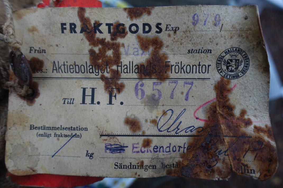 En gammal etikett med snirklig handsstil och gammalmodig tryckt text.