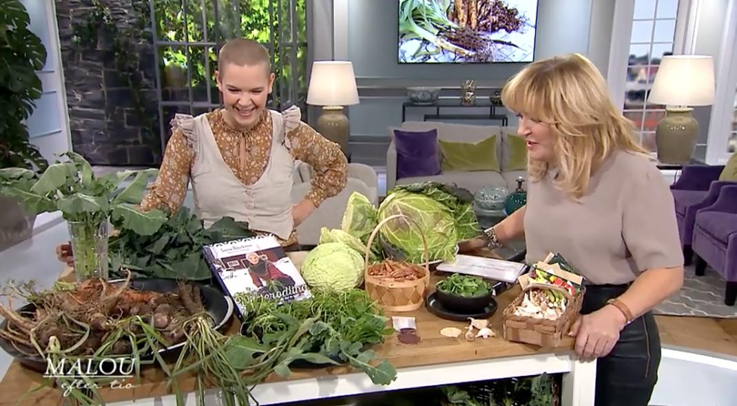 Sara och Malou von Siwerts står vid ett bord med massor av grönsaker på.