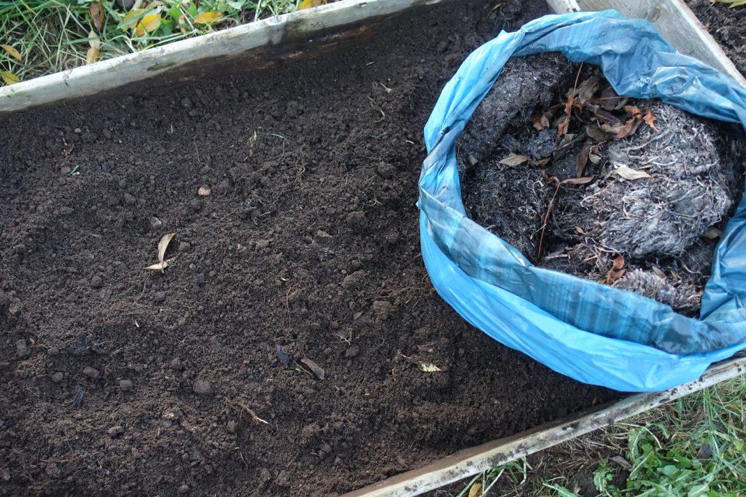 En pallkrage sedd ovanifrån med bar jord, en blå säck med tång står i ett hörn.