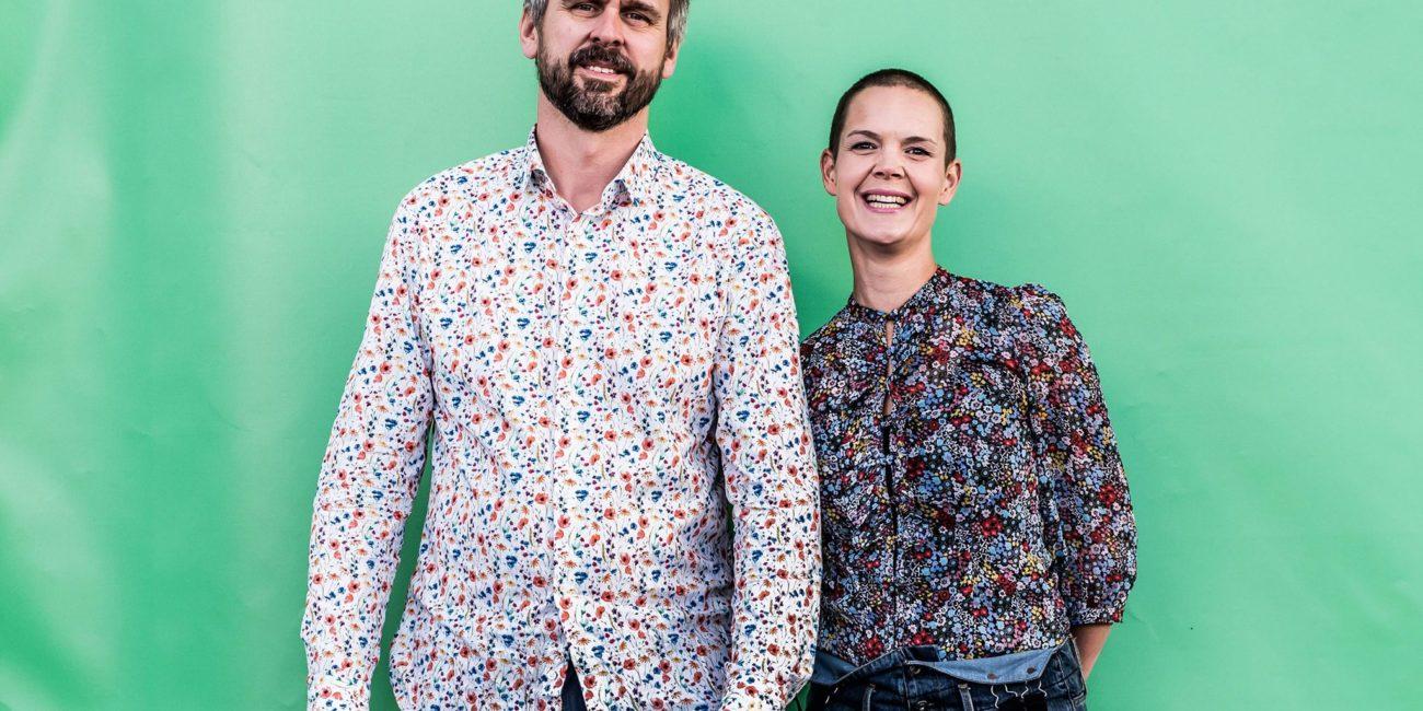 Sara och Johannes i blommiga kläder mot en turkos bakgrund.