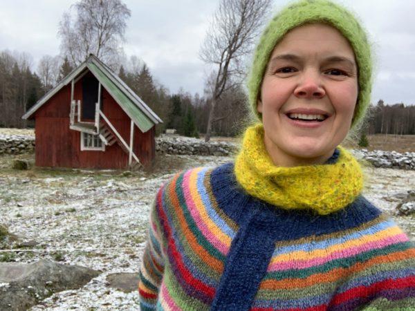 Sara med ett stort leende framför vintergrå trädgård.