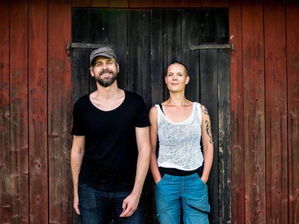 Sara och Johannes står framför en röd ladugård med svart dörr.