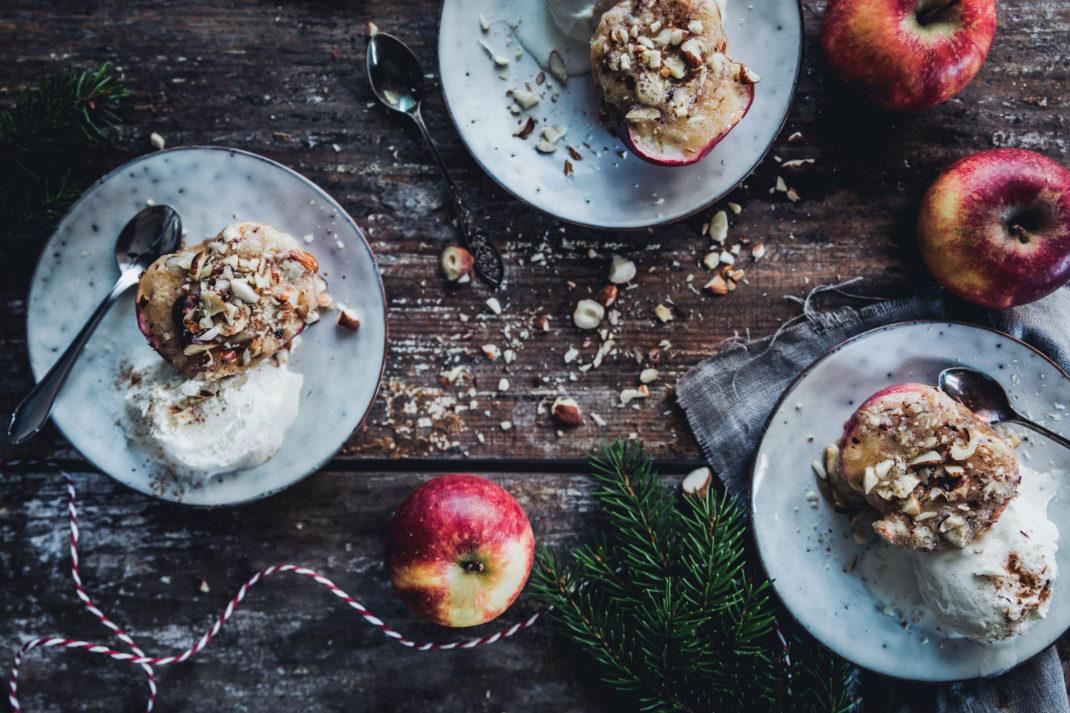 På tallrikar ligger vakcra äppelhalvor med amndelmassa, nötter och glass.