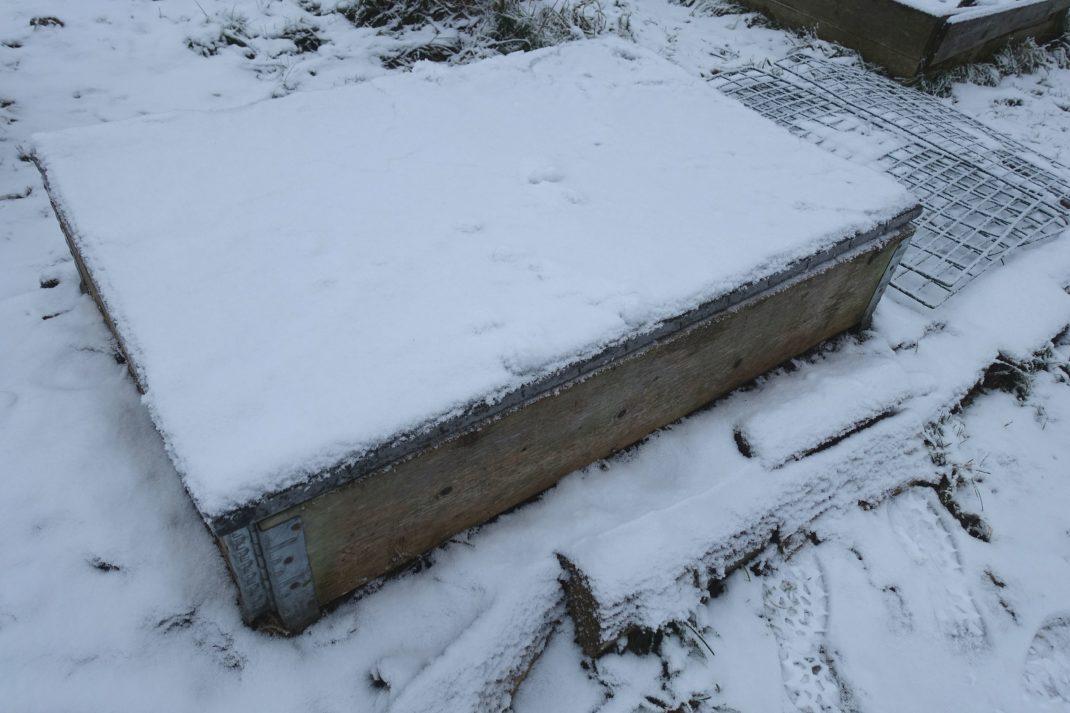 En pallkrage med lock på en snötäckt bädd.
