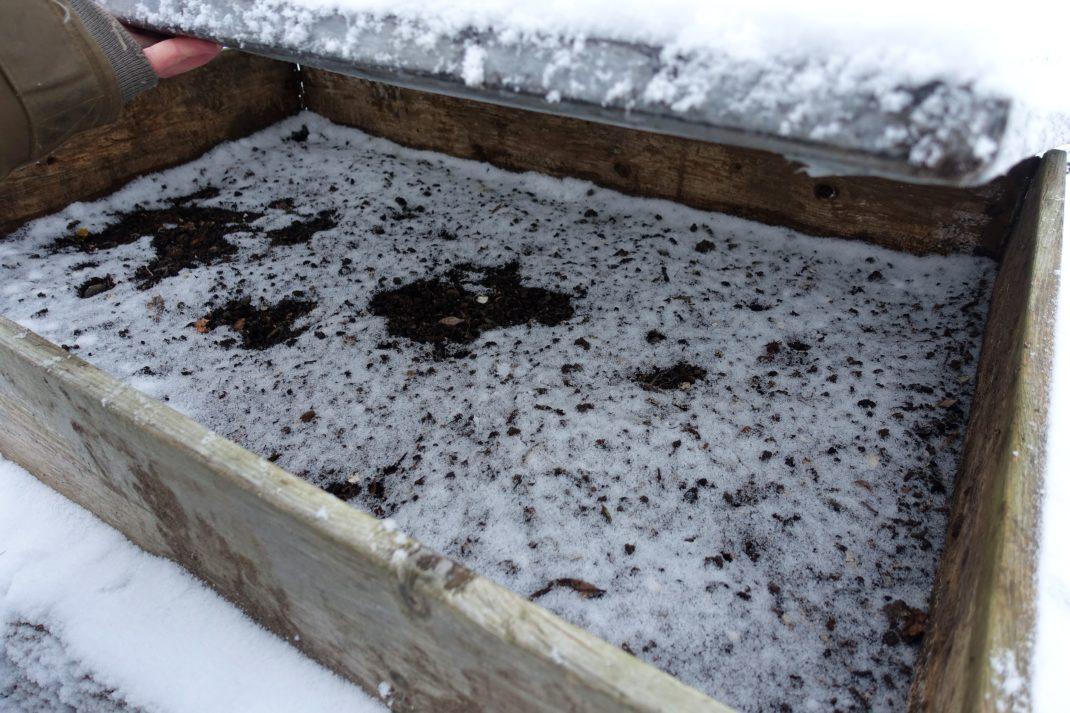Under locket finns jord som är täckt av ett puder med snö.