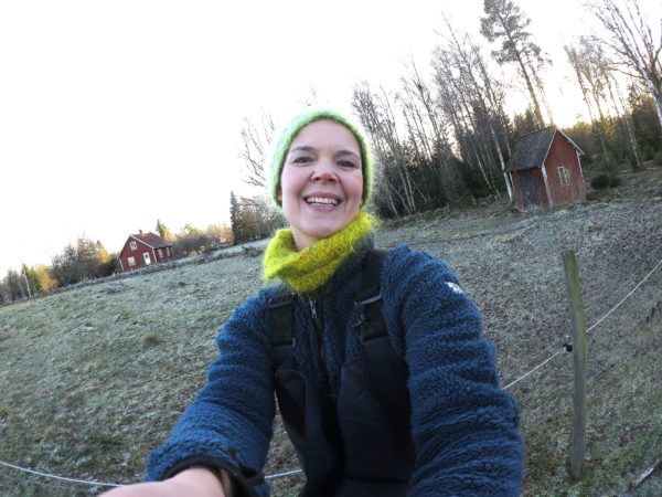 Sara Bäckmo står i trädgården med beteshagen bakom sig, vinter.