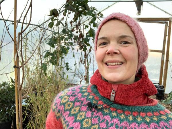 Sara med en glad min i tunnelväxthuset, på sig har hon stickad mössa och islandströja.