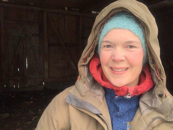 Sara har flera lager kläder på sig och ser glad ut i en kall bod.