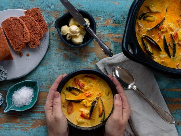 Guldgul fisksoppa i fina skålar mot ett avskavt blått trädbord.