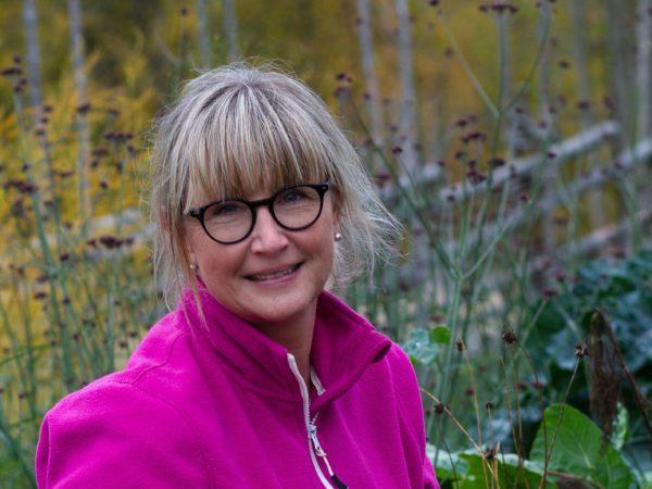 En kvinna i rosa fleecetröja i en färgrik höstträdgård.
