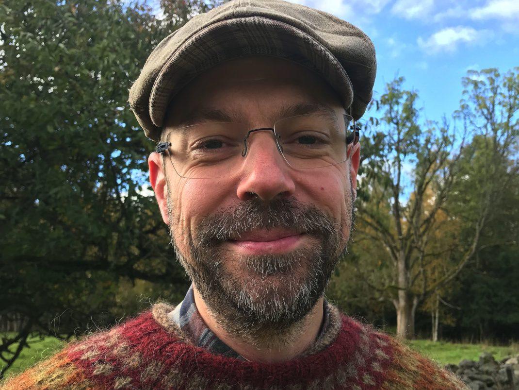 En man i stickad tröja och keps, med lite skägg och glasögon, fotograferad ute i naturen.