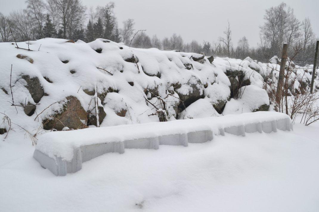 Ett snötäckt landskap med stenmur och ett land som anas under snön.