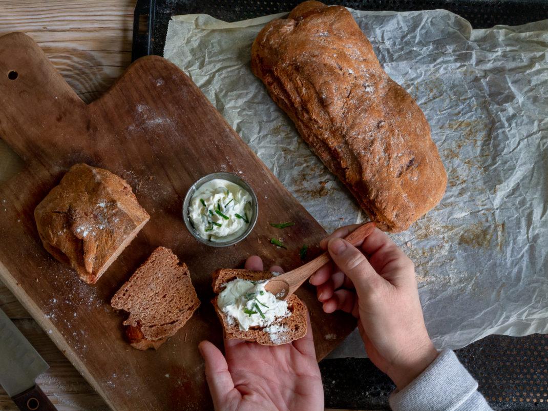 Två händer brer röra på en skiva av mörkbrunt bröd.