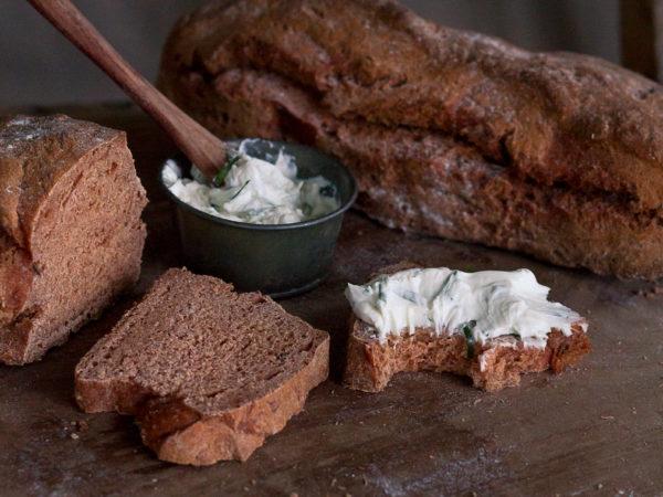 Läckert brun brödlimpa är uppskuren och serverad med färskost.