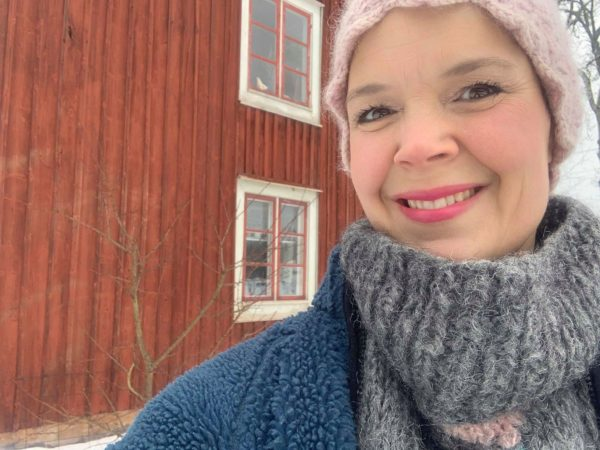 Sara framför vintrigt Skillnadens hus.