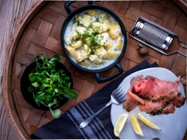 Stuvad potatis med gravad lax med färskt grönt.