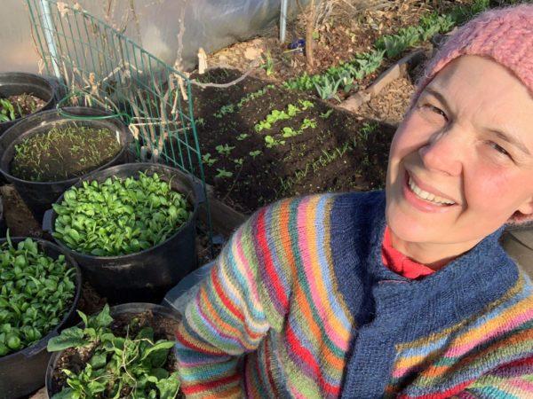Sara i vackert stickad kofta framför krukor som gror i tunnelväxthuset.