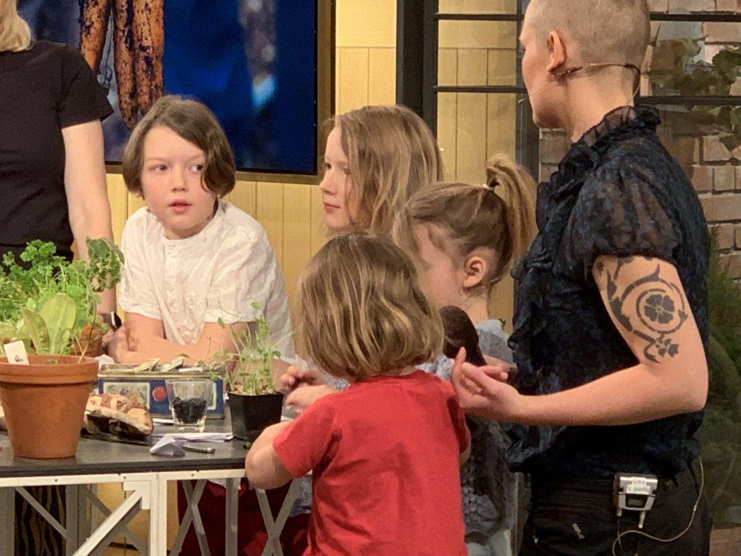 Bild från intervjun där alla står uppställda vid ett bord.