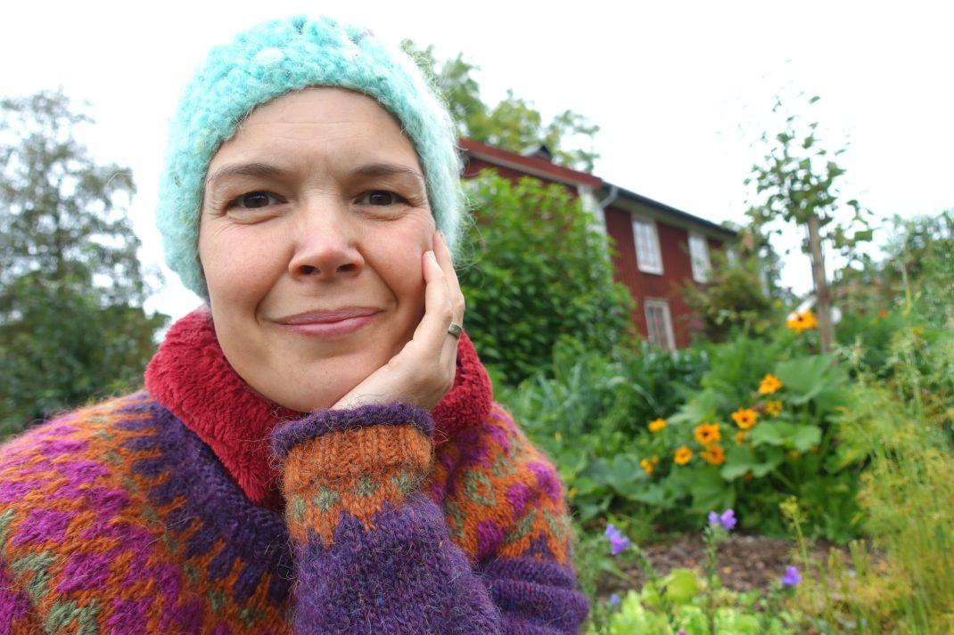 Sara Bäckmo sitter i en sensommarköksträdgård.