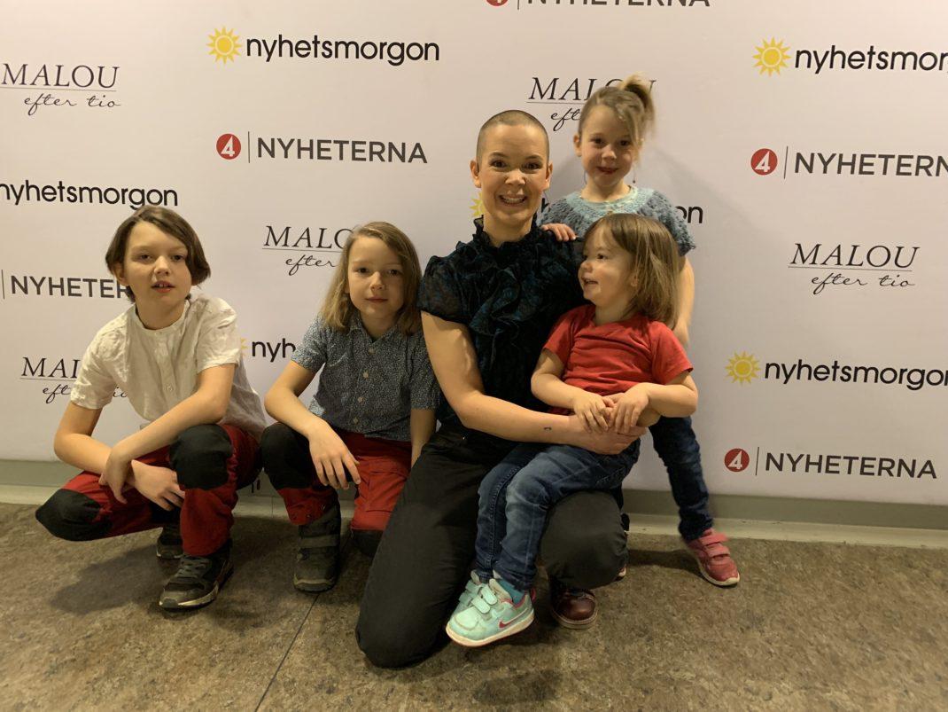 Gruppgild på Sara och barnen framför programloggor på en vägg.