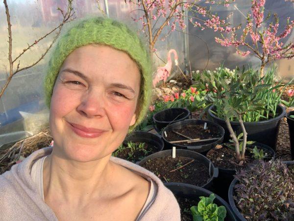 Sara i grön mössa med rosablommande fruktträd i bakgrunden.