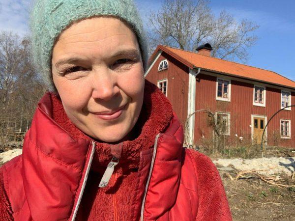 Sara med röd jacka i ett soligt Skillnadens Trädgård.
