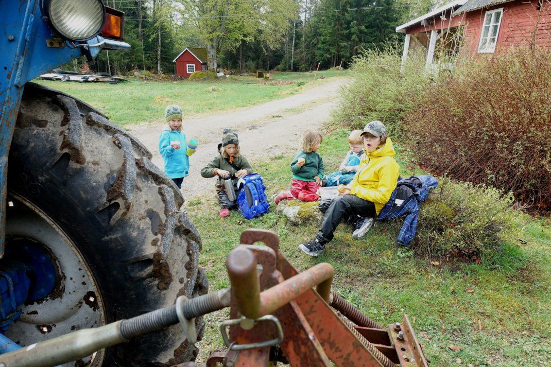Barn sitter bakom en traktor i regnkläder och fikar.