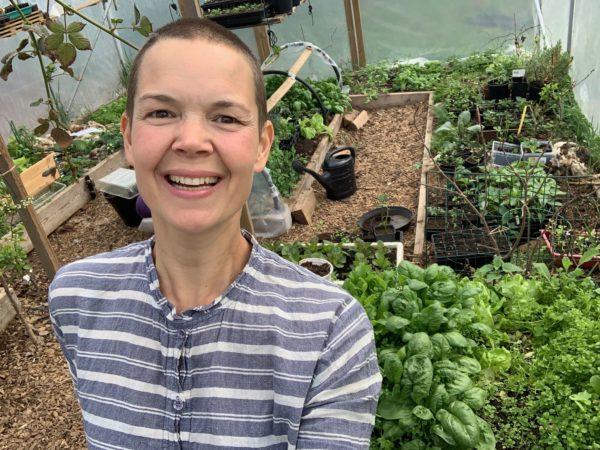 Sara i randig skjorta står i ett grönskande tunnelväxthus