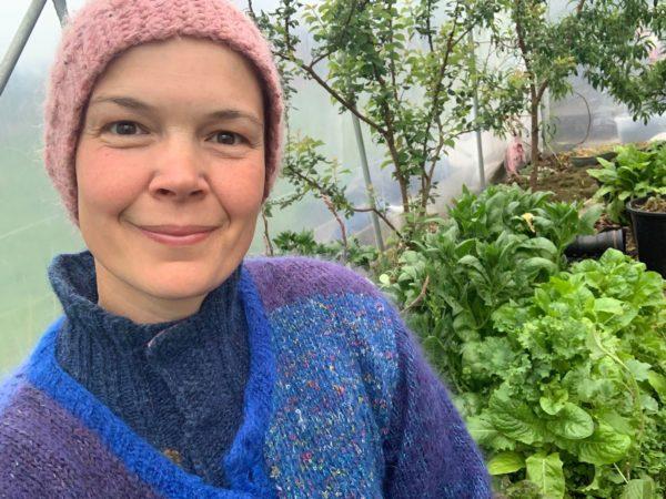 Sara i tre lager stickat njuter av ett grönt tunnelväxthus.