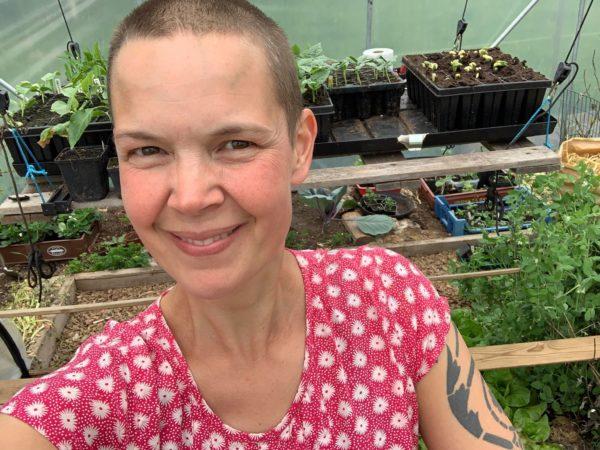 Sara i prickig tröja i växthuset.