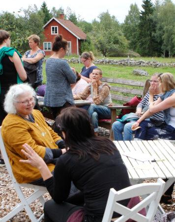 Sara sitter med medlemmar som är på studiebesök i Skillnadens Trädgård.