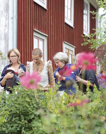 Sara står med medlemmar som är på studiebesök i Skillnadens Trädgård.