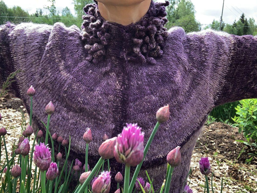 Sara med utfällda armar i lila kofta och gräslöken som blommar i förgrunden.