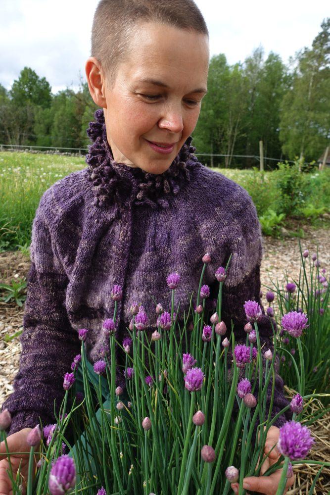 Sara sitter vid blommande gräslök. My puff sleeve cardigan.